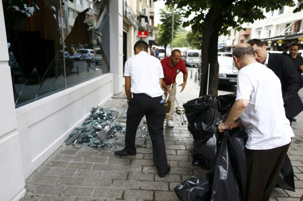 Рабочие из близлежащих магазинов убирают осколки витрин, пострадавших в результате взрыва.
