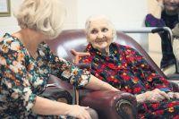 Гериатр проводит обследование пожилых людей.