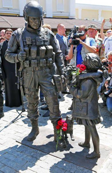 Скульптура представляет собой бронзовую композицию из трех фигур – военного, девочки и кота. Общая высота монумента – 2,2 метра, вес – больше тонны
