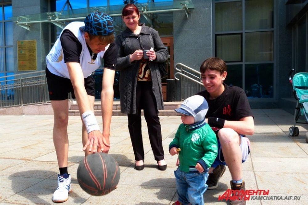 Малыша завораживают трюки, которые спортсмен делает с помощью мяча.