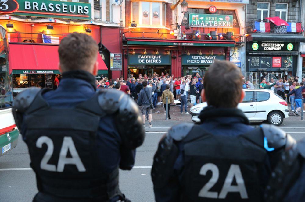 Сотрудники полиции наблюдают за болельщиками у бара на одной из улиц во французском городе Лилле.