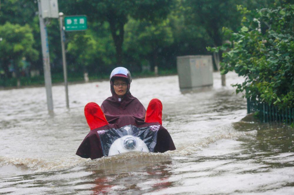 Женщина на одной из затопленных улиц в Лючжоу.