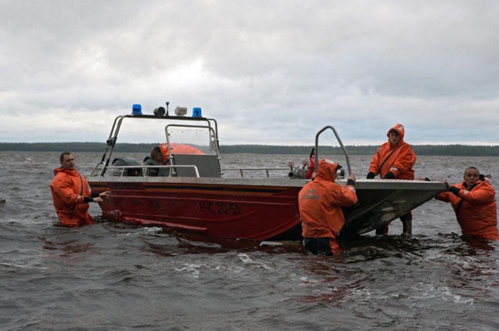 Спасатели спускают лодку на воду на месте проведения поисково-спасательной операции в районе озера Сямозеро в Карелии, на котором в туристическом походе во время шторма погибли дети.