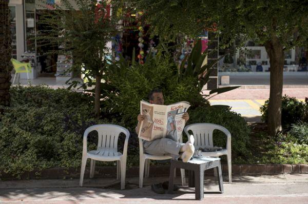 Мужчина читает газету на улице в Кемере.