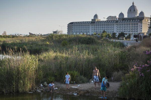 Местные жители ловят рыбу рядом с отелем в Анталье.