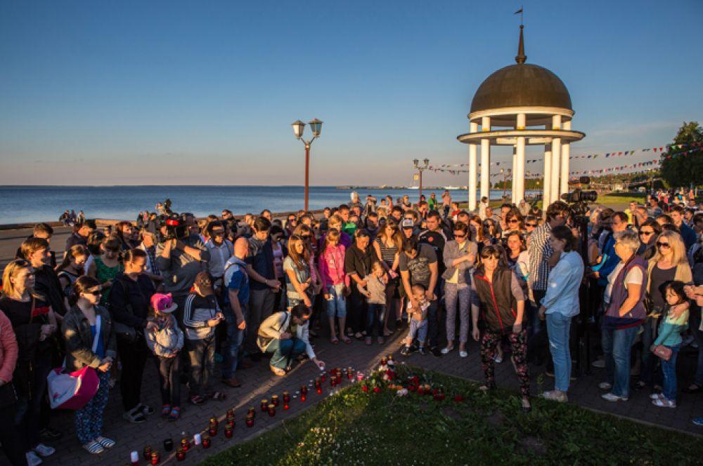 Люди на набережной в Петрозаводске во время акции в память о детях, погибших при шторме на Сямозере в Карелии.