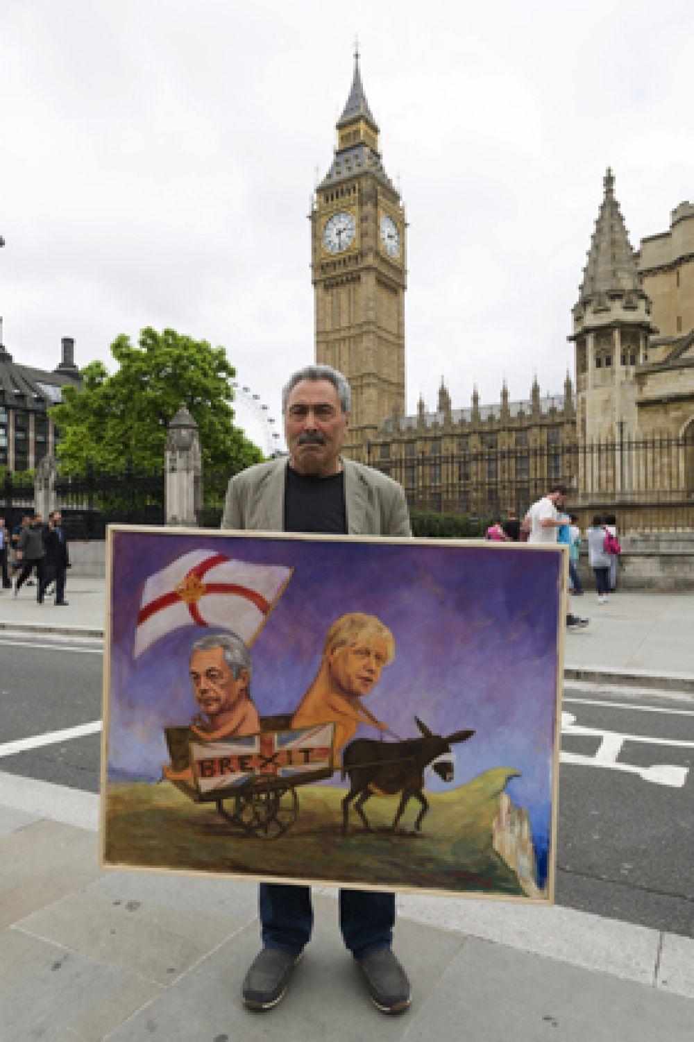 Мужчина с агитационным плакатом на улице Лондона перед предстоящим референдумом.
