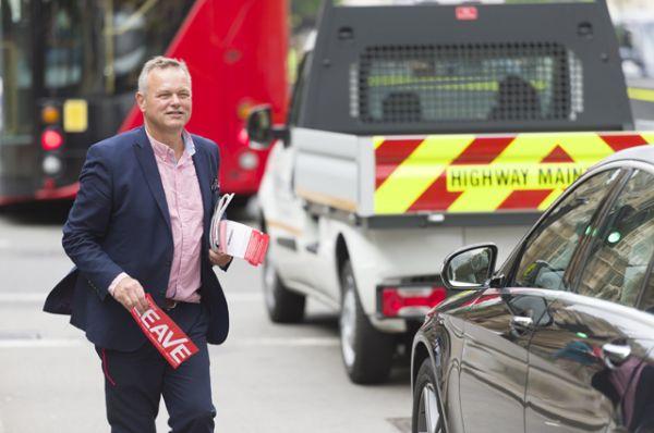 Мужчина раздает агитационные листовки перед предстоящим референдумом.