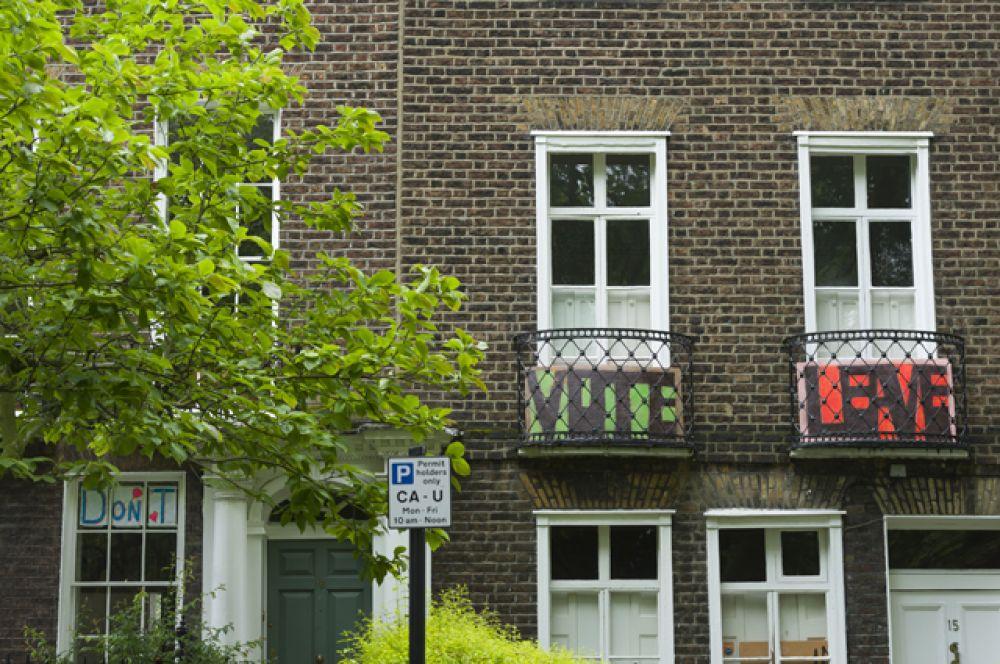 Надписи Vote и Leave на балконах жилого дома на улице Хайгейт Роуд в Лондоне в день референдума в Великобритании по сохранению членства в Европейском Союзе.