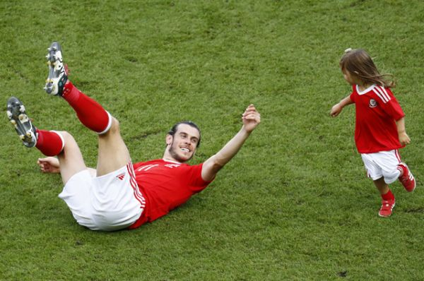 Нападающий сборной Уэльса Гарет Бейл со своей дочерью Альбой празднует победу.
