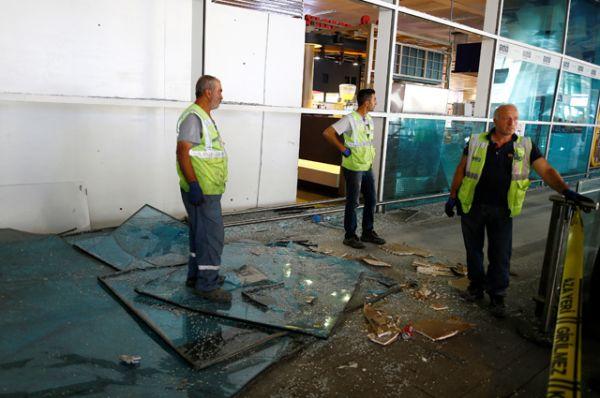 Рабочие убирают осколки стекол на месте взрыва.