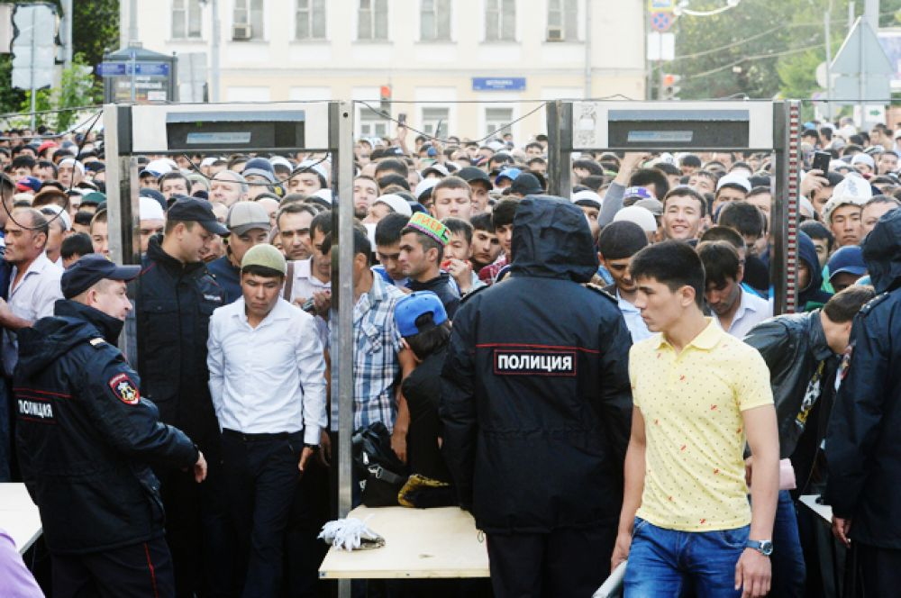 Мусульмане проходят через рамки металлоискателя перед намазом в день праздника Ураза-байрам у Соборной мечети в Москве.
