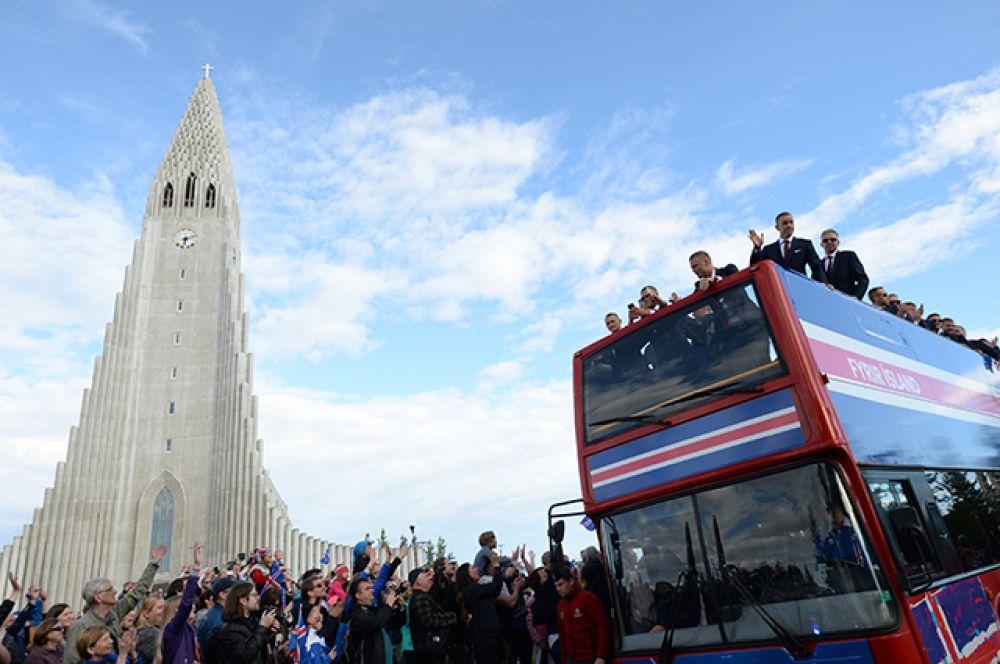 Футболисты сборной Исландии, прибывшие в Рейкьявик, приветствуют фанатов.