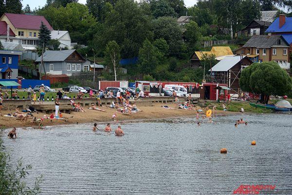 На пляже у Мотовилихинского пруда даже в будний день в полдень довольно многолютно.