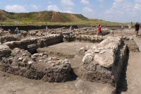 Остатки здания из камня на раскопе «Нижний город». На заднем плане - бывший акрополь Фанагории, который теперь напоминает обычные холмы.