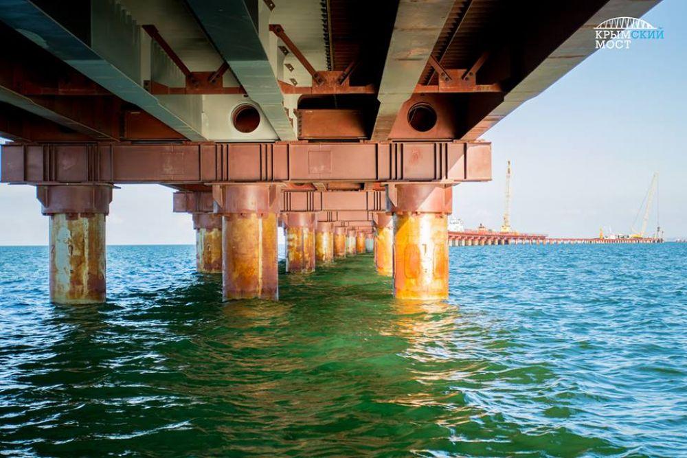 Рабочие мосты спокойно выдерживают тяжелую технику и позволяют строить в любую погоду, даже в шторм. Многие принимают временные сооружения за Крымский мост.