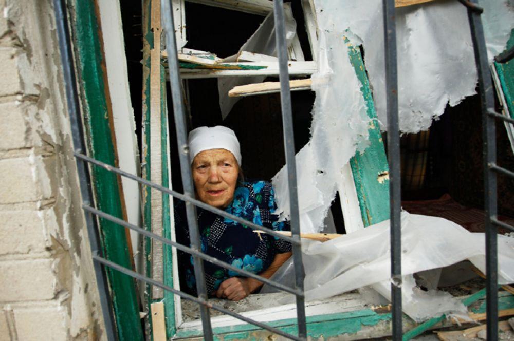 Пенсионерка в окне разрушенного дома.