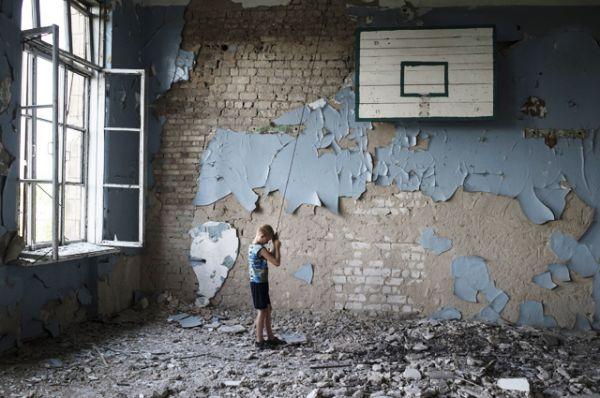 Подросток играет в разрушенном спортивном зале средней школы поселка Шахты 6/7, ставшей убежищем для местных жителей.