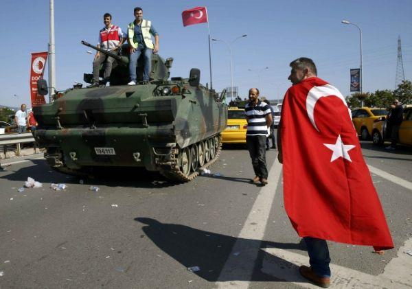 Человек, завернутый в турецкий флаг, проходит мимо военного автомобиля возле аэропорта Сабиха.
