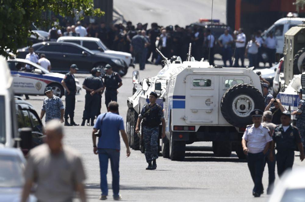 К зданию полиции, где удерживают заложников, стянуты полицейские и спецтехника (БТР).