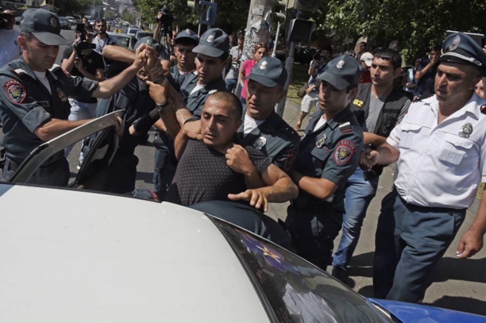 Полицейские сажают в машину задержанного у захваченного здания отделения полиции в районе Эребуни на окраине Еревана.