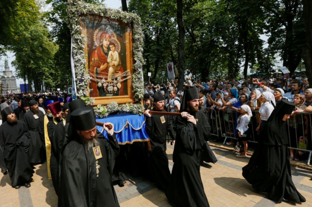 У монастыря верующих встречают монахи с иконами.