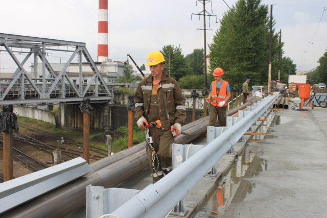 Рабочие завершают ремонт полосы на мосту на улице Суворова в Калининграде.