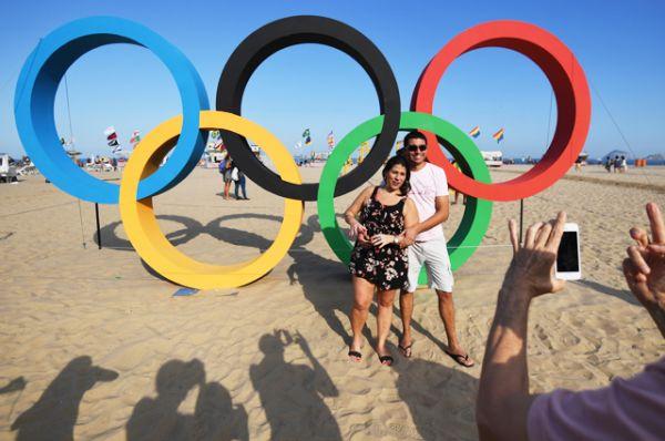 Отдыхающие фотографируются у олимпийских колец на пляже Копакабана в Рио-де-Жанейро.