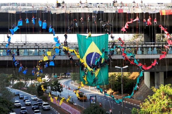 Люди свешиваются с моста в Сан-Паулу, образуя олимпийские кольца.