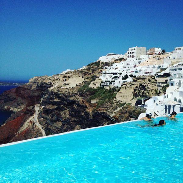 Бассейн с видом на город на холмах и Эгейское море в Санторини. Находится возле отеля Katikies