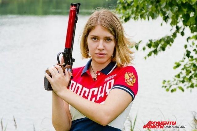 Девушка занимается стрельбой из пневматического пистолета.