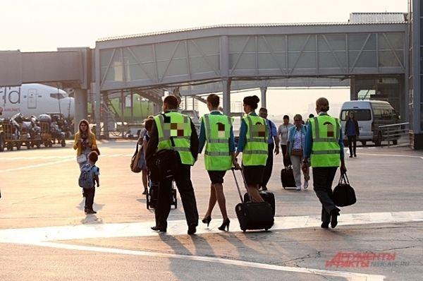 В лучах утреннего солнца на борт спешат стюарды и стюардессы.