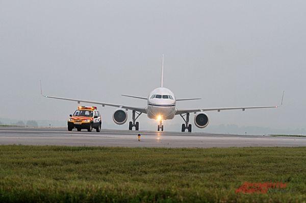 Приземлившиеся большие самолёты курсируют за машиной сопровождения.