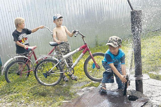 Городские дети охлаждаются в фонтанах, деревенские - в реке и на колонке.