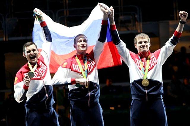 Алексей Черемисинов (крайний справа) с золотой медалью Олимпиады.