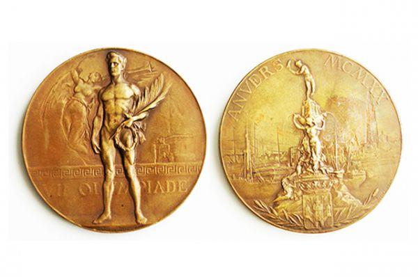 1920 год, Игры в Бельгии. На лицевой стороне медали — атлет, держащий лавровый венок и пальмовый лист, на оборотной стороне статуя Сильвиуса Брабо. На ребре выгравировано имя чемпиона, название соревнования, команда и дата.