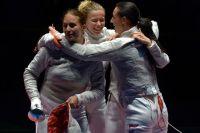 Спортсменки сборной Росиии Софья Великая, Юлия Гаврилова и Яна Егорян (слева направо) радуются победе в финальном поединке командного первенства по фехтованию на саблях среди женщин против команды Украины на XXXI летних Олимпийских играх.