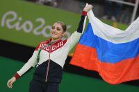 Алия Мустафина (Россия), завоевавшая золотую медаль в упражнениях на брусьях на соревнованиях по спортивной гимнастике среди женщин на XXXI летних Олимпийских играх, на церемонии награждения.