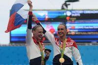 Светлана Ромашина и Наталья Ищенко (Россия), завоевавшие золотые медали на соревнованиях по синхронному плаванию среди дуэтов на XXXI летних Олимпийских играх, во время церемонии награждения.