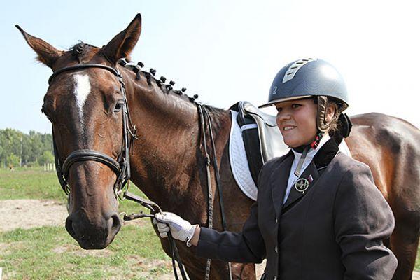 Сразу после выступления Полина Исаева немного уставшая, но довольная. «Я занимаюсь конным спортом 5 лет. Когда пришла в него мне было 12, - делится наездница. - Моего коня зовут Тайна. Мы с ним всего год вместе занимаемся. Характер у него не простой, очень темпераментный и приходиться приструнять его».
