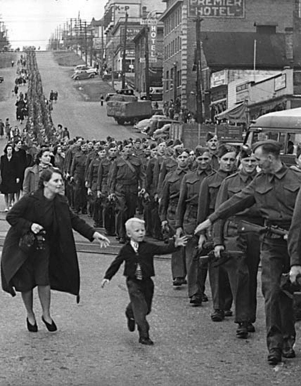 «Подожди меня, папа» — фотография марша полка Британской Колумбии в Нью-Уэстминстере в Канаде, сделанная Клодом П. Деттлоффом 1 октября 1940 года. Пока Клод делал снимок, пятилетний Уоррен Бернард убежал от своей матери к отцу, рядовому Джеку Бернару, с криком «Подожди меня, папа».