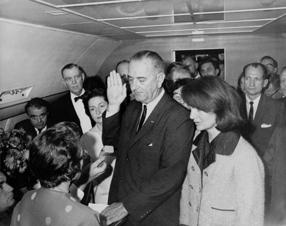Присяга Линдона Джонсона на борту Air Force One в день убийства Кеннеди. Президента окружают три женщины: справа — овдовевшая Жаклин Кеннеди, слева — его собственная жена, прозванная Lady Bird, перед ним с Библией в руке — судья Сара Хьюз, единственная женщина в истории, принявшая присягу у президента США. 22 ноября 1963 года.