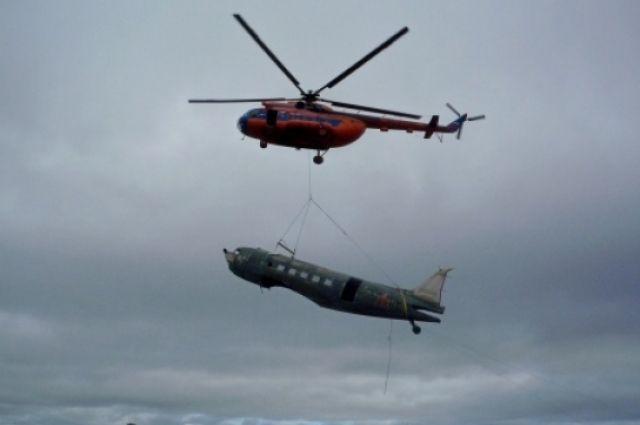 Самолет транспортировал на внешней подвеске вертолет Ми-8.