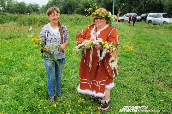 Девушки и женщины плели венки из полевых цветков на конкурс.