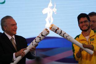 И. о. президента Бразилии Мишел Темер (слева) зажигает огонь Паралимпиады.