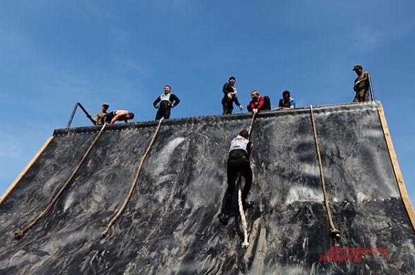 Преодоление наклонной стены - не простое препятствие. Все участники в мокрых костюмах и многие скользят и скатываются вниз. Силы рук не хватает и женщинам, и мужчинам. Но участники помогают забраться наверх.