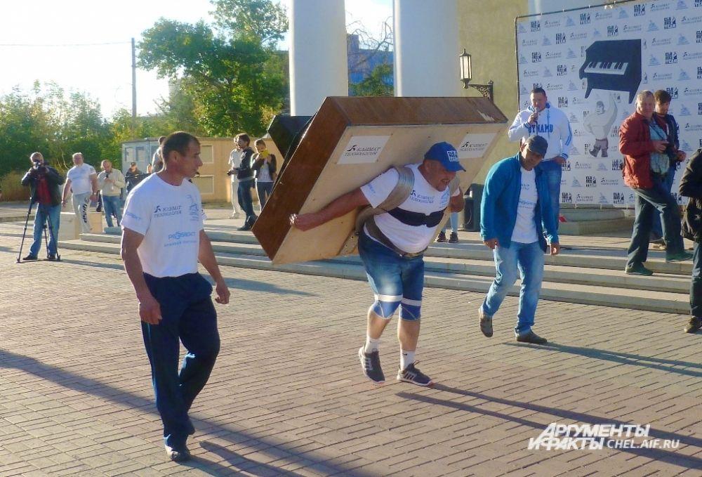 На площадке в 30 метрах друг от друга были установлены деревянные тумбы, спортсмен с пианино на плечах доходил до одной из них, разворачивался и шёл обратно.