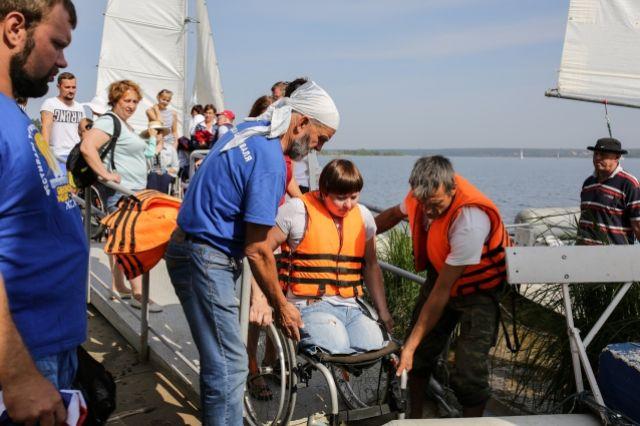 Анатолий Кулик помогает инвалидам занять места на тримаранах