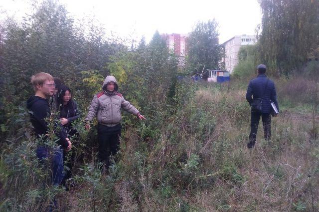 Предполагаемый убийца ( в куртке с капюшоном) указывает на место преступления.