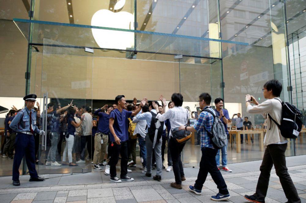 Менеджеры и продавцы магазина в Токио приветствуют первых покупателей.